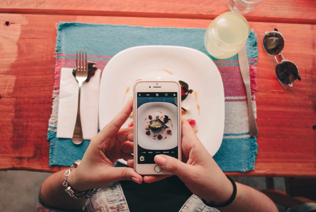 iphone taking photo of plate of food