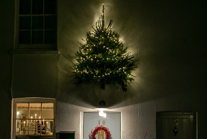 lit christmas tree attached to house