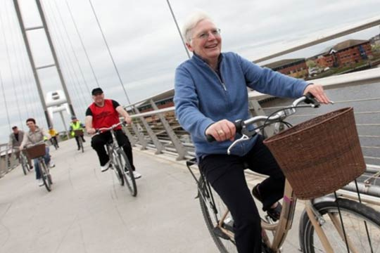 Old people cycling across a bridge