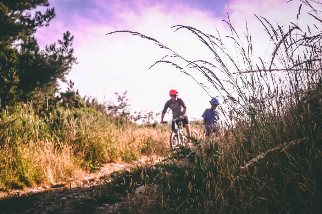 2 people cycling on country path