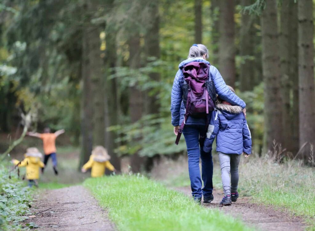 women and child walking in woods with other child playing